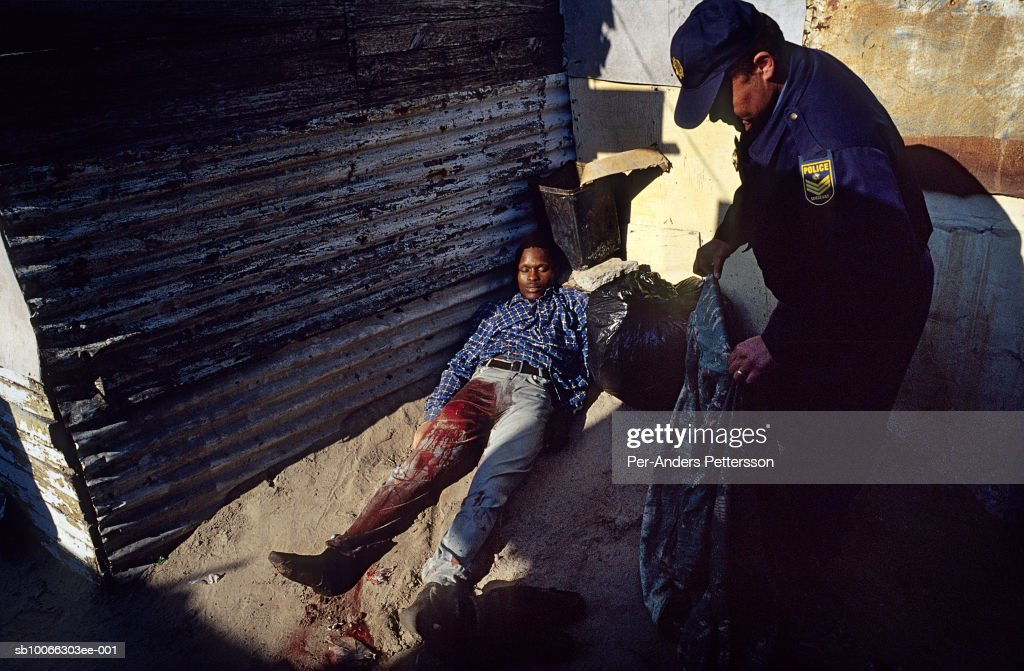 South Africa, Cape Town, Khayelitsha, police officer places blanket over dead man outside shack : News Photo