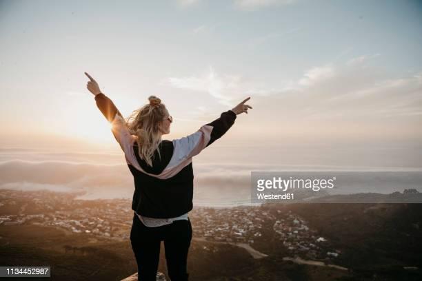 south africa, cape town, kloof nek, happy woman enjoying the view at sunset - euphorique photos et images de collection