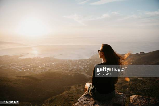 south africa, cape town, kloof nek, woman sitting on rock at sunset - espalda chica morena playa fotografías e imágenes de stock