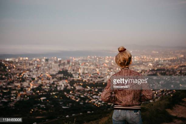 south africa, cape town, kloof nek, woman woman looking at cityscape at sunset - observation point stock pictures, royalty-free photos & images