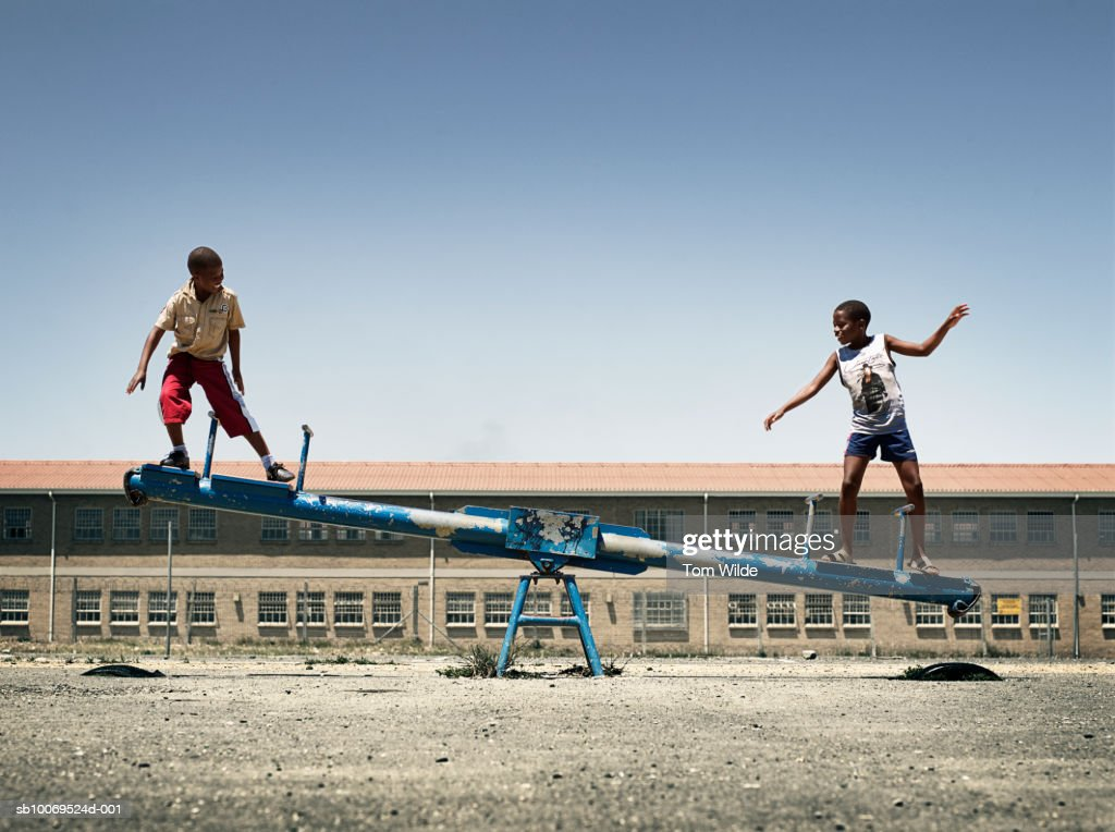 South Africa, Cape Town, Langa, boys (12-14) balancing on seesaw : Stock Photo