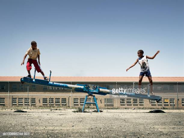 South Africa, Cape Town, Langa, boys (12-14) balancing on seesaw