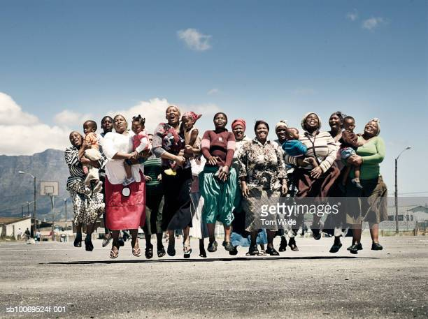 South Africa, Cape Town, Langa, group portrait of girls and women with children (2-4) jumping