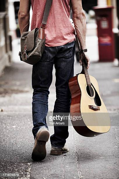 South Africa, Cape Town, Man with guitar walking down street