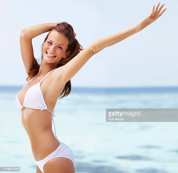 South Africa, Cape Town, Portrait of young woman in bikini, arms raised