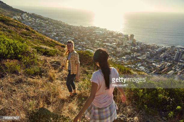 South Africa, Cape Town, Signal Hill, two young women hiking above the city