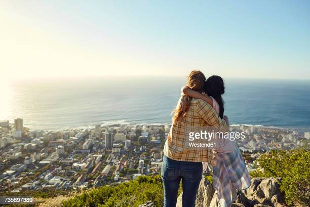south africa, cape town, signal hill, two young women hugging overlooking the city and the sea - aussichtspunkt stock-fotos und bilder