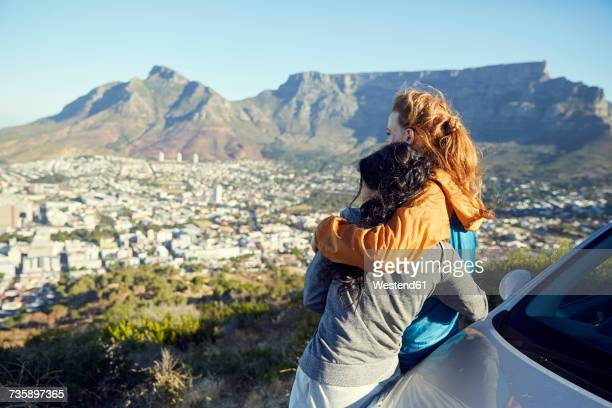 south africa, cape town, signal hill, two young women leaning against car overlooking the city - table mountain stock pictures, royalty-free photos & images