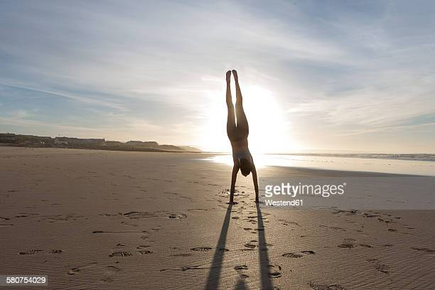 South Africa, Cape Town, silhouette of young woman doing handstand on the beach