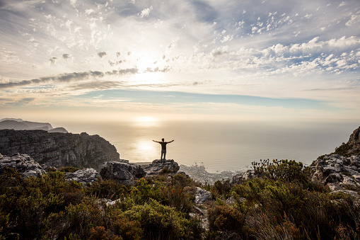 South Africa, Cape Town, Table Mountain, man standing on a rock at sunset - gettyimageskorea