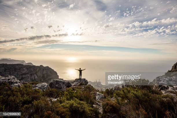 south africa, cape town, table mountain, man standing on a rock at sunset - スピリチュアル ストックフォトと画像