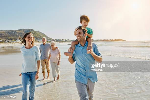 South Africa, Cape Town, three generations family strolling on the beach