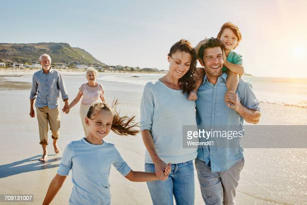 south africa, cape town, three generations family strolling on the beach - multigenerational family stock photos and pictures