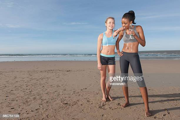 South Africa, Cape Town, two joggers taking a break on the beach