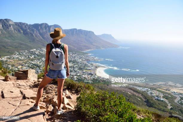 South Africa, Cape Town, woman standing looking at the coast during hiking trip to Lion's Head