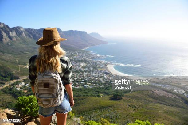 south africa, cape town, woman standing looking at the coast during hiking trip to lion's head - table mountain stock pictures, royalty-free photos & images