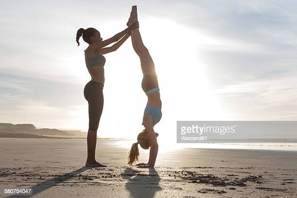 South Africa, Cape Town, young woman helping her friend doing handstand on the beach