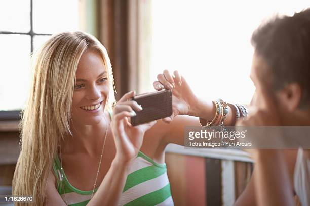 South Africa, Cape Town, Young woman taking picture with cell phone
