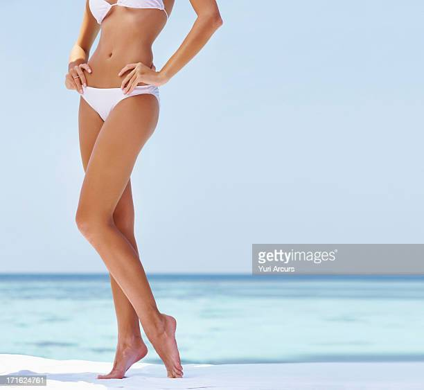 South Africa, Cape Town, Young woman wearing bikini, low section
