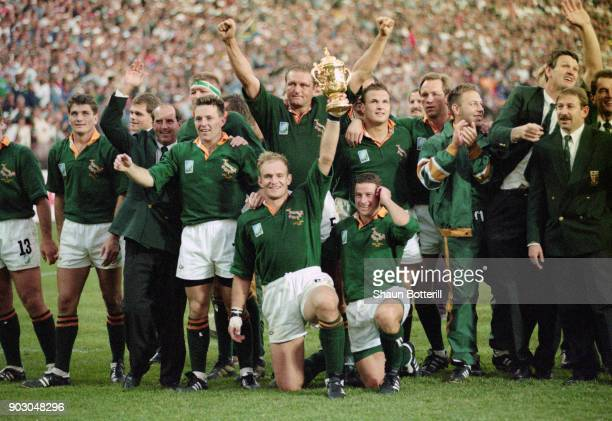 South Africa captain Francois Pienaar holds aloft the Webb Ellis trophy as the rest of the team celebrate after their 1995 World Cup Final victory...