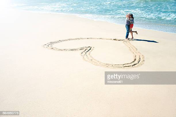 South Africa, couple embracing in front of heart carved in the sand of the beach