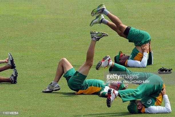 South Africa cricketers Faf du Plessis AB de Villiers and Colin Ingram stretch during a training session at The Shere Bangla National Stadium in...