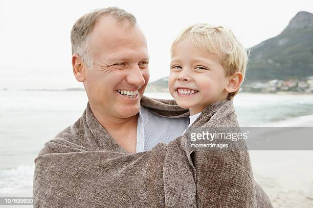South Africa, Father carrying son (4-5) on beach