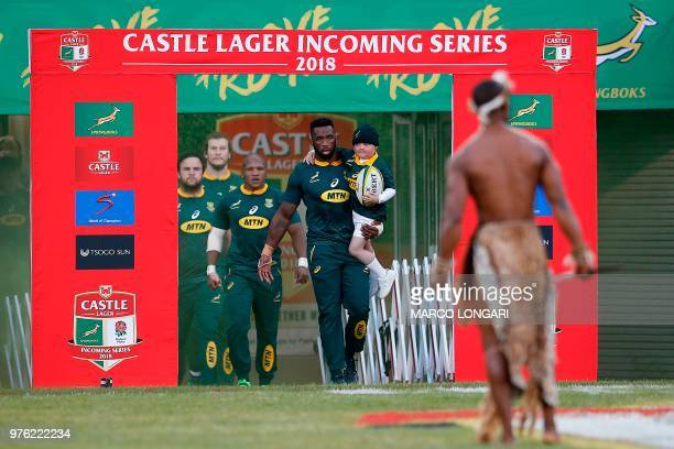 South Africa flanker and captain Siya Kolisi enters the field holding his son Nicholas prior to the second test match South Africa vs England at the...