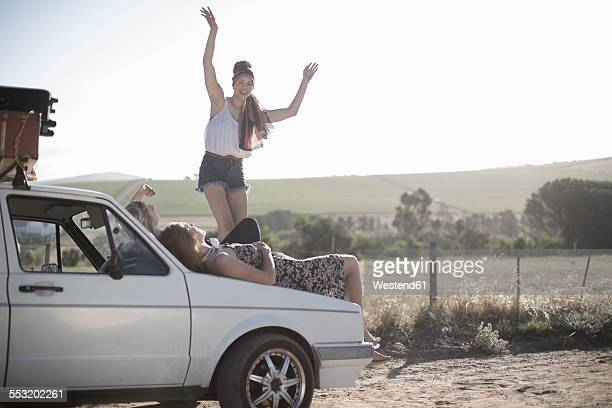 South Africa, Friends on a road trip resting on car bonnet