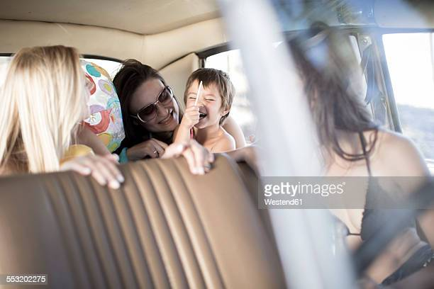South Africa, Friends on road trip sitting in car with little girl