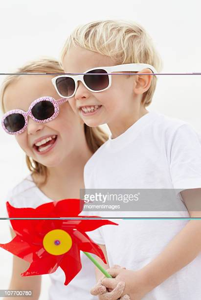 South Africa, Girl (10-11) and boy (4-5) wearing sunglasses on beach
