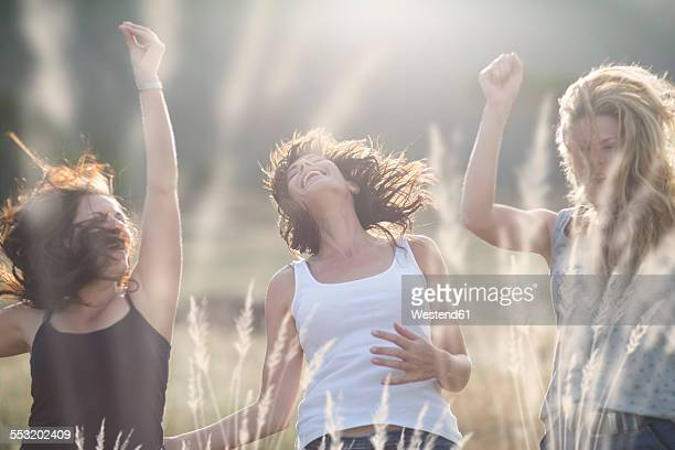 South Africa, Girl friends dancing and jumping in field