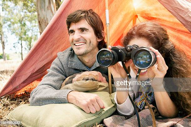 South Africa, happy couple with binoculars in tent