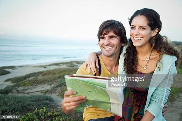 South Africa, happy couple with map embracing at the coast