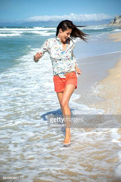 South Africa, happy woman running along the beach at seafront