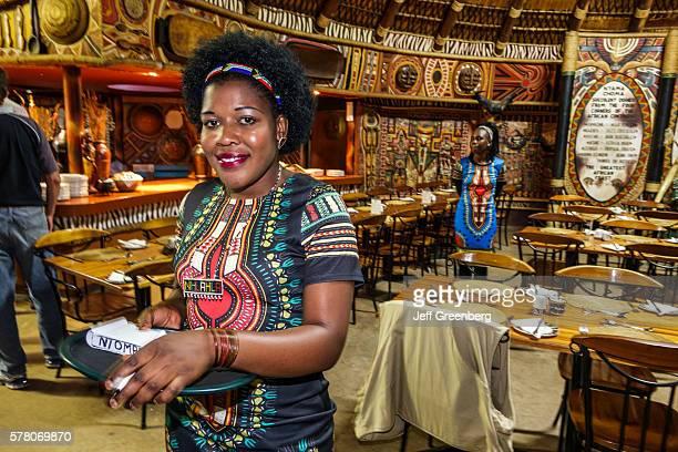 South Africa Johannesburg Lesedi Lodge Cultural Village Zulu Xhosa Pedi Basotho Ndebele tribes Nyama Choma restaurant inside woman waitress employee...