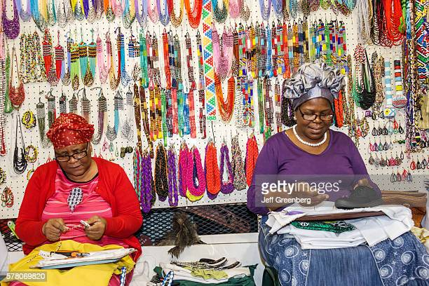South Africa Johannesburg Rosebank Mall The Flea Market shopping sale display arts crafts vendor stall woman beads making necklaces