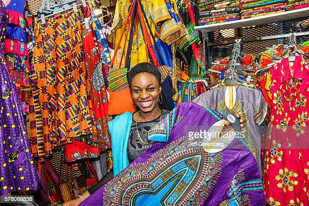 South Africa Johannesburg Rosebank Mall The Flea Market shopping sale display arts crafts vendor stall man woman couple looking clothing dashiki gown