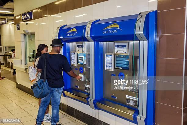 South Africa Johannesburg Rosebank Station Gautrain mass rapid transit railway system selfservice ticket vending machine man woman couple using buying