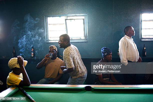 South Africa, Johannesburg, Soweto, group of men drinking and smoking in bar