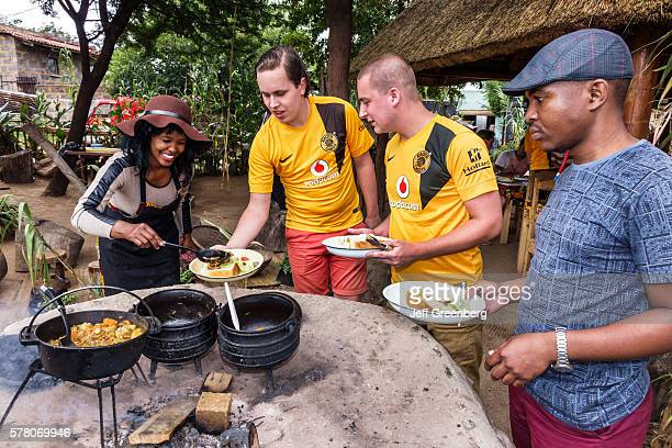 South Africa Johannesburg Soweto Lebo's Backpackers Hostel woman cooking cook kettle serving lunch man
