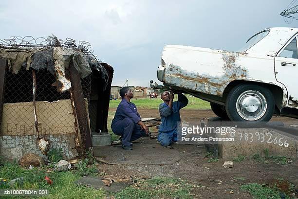 South Africa, Johannesburg, Soweto, two man repairing car