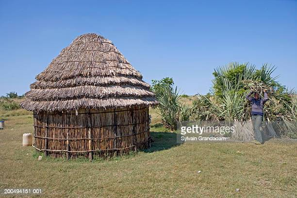 South Africa, Kwazulu-Natal, person beside traditional Zulu hut