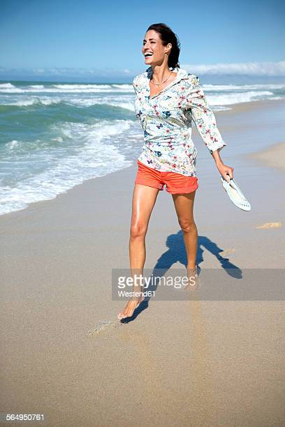south africa, laughing woman walking along the beach - pies descalzos mujer fotografías e imágenes de stock