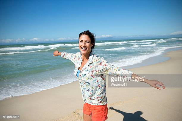 south africa, laughing woman with outstretched arms standing on the beach - blue blouse stock pictures, royalty-free photos & images