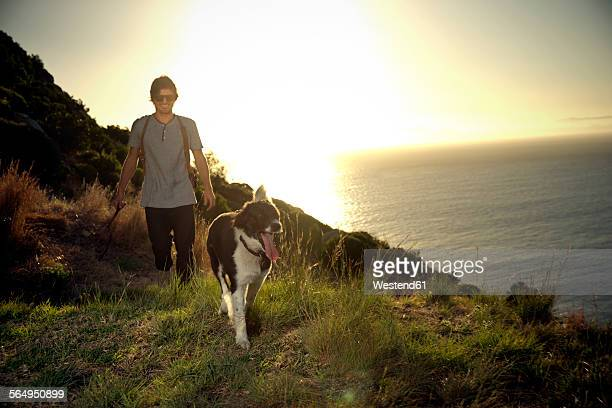 South Africa, man walking along the coast with his dog at evening twilight
