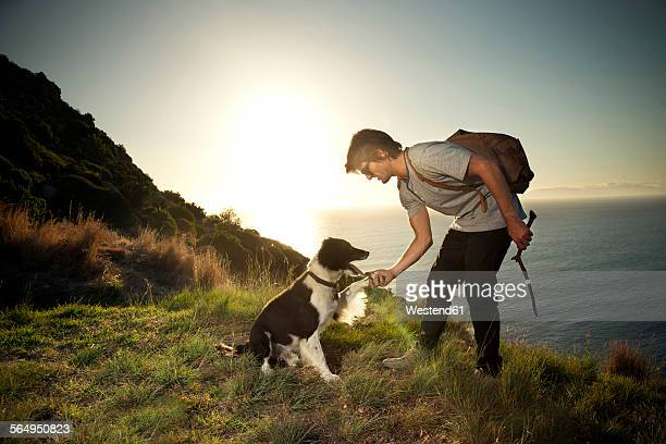 South Africa, man with dog at the coast at sunset