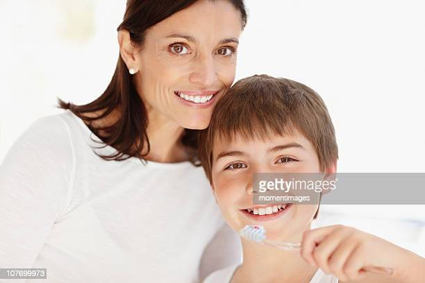 South Africa, Mother embracing son (12-13)  while he is brushing teeth