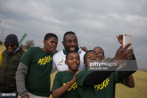 TOPSHOT South Africa national Springbok player Tendai Mtawarira poses with aspiring rugby players from nearby high schools during a rugby clinic...