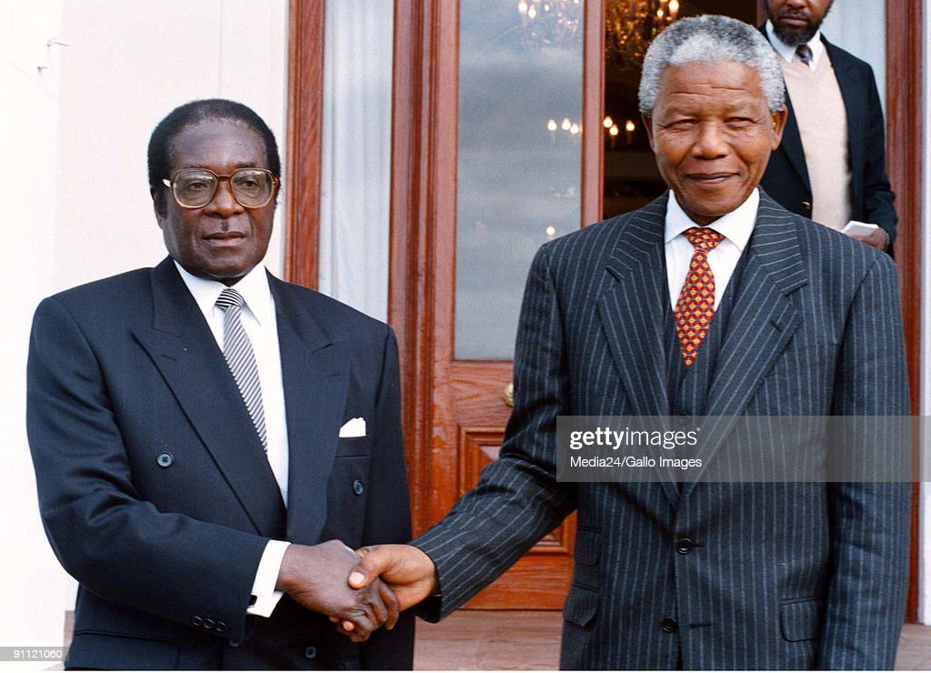South Africa. Nelson Mandela as President, pictured with Zimbabwean president, Robert Mugabe during a state visit.. : News Photo